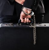 Businessman wearing a suit with a secure suitcase attached with handcuffs